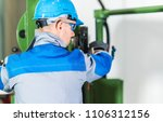 Professional Heavy Duty Machinery Operator. Caucasian Metalworking Industry Worker in Blue Hard Hat in Front of Machine Console. Industrial Theme. - stock photo