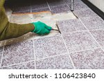 Small photo of dismantling of tile. Hands in green working gloves undermine the broken tile with a chisel.