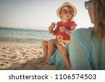 little girl and mom on sandy... | Shutterstock . vector #1106574503
