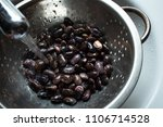 Small photo of Kyiv, Kyiv Oblast / Ukraine - 21 01 2018: horizontal photo of beans that are rinsed with a stream of water through a sieve in a white sink