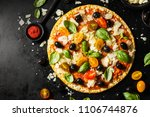 Top view of tasty appetizing classic italian traditional pizza with cheese, olives, basil and fresh vegetables on dark black table.