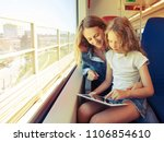 Small photo of Woman with child traveling by pablic transport. Family travelling in a train and looking through the window