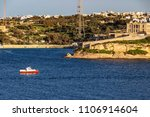 Small photo of A red and white motorboat passes along the Kalkara coastline, Rinella Bay Kalkara Malta, part of the Bighi Complex