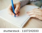 kid holding pen and writing in... | Shutterstock . vector #1107242033
