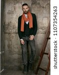 Small photo of Full length isolated studio portrait of a young handsome man in grey jeans, a black cardigan and a terra cotta scarf. The stylish bearded guy standing, posing over the grunge rusty background.