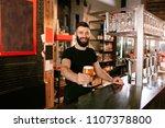 bartender with beer in glass in ... | Shutterstock . vector #1107378800