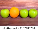 an orange between apples ... | Shutterstock . vector #1107400283