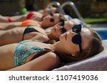 four young women sunbathing in... | Shutterstock . vector #1107419036