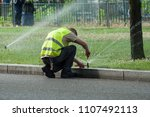 transportation company employee adjusting automatic sprinklers on tramway line - stock photo