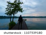 fisherman on wooden pier during ... | Shutterstock . vector #1107539180