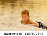 baby boy playing with sand on... | Shutterstock . vector #1107577646
