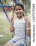 asian teenager sitting on swing ... | Shutterstock . vector #1107579389