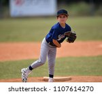 Young Boy Pitching The Ball In...