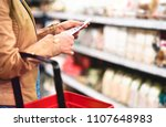woman in supermarket aisle with ... | Shutterstock . vector #1107648983
