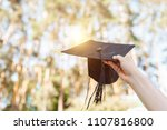 Small photo of Successful graduate, in academic dresses, raised up graduation cap, farewell study, can be used for advertising