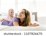 happy mother with baby lying on ... | Shutterstock . vector #1107826670