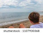 child sitting on the sand near... | Shutterstock . vector #1107930368