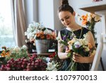 florist arranging a bouquet of... | Shutterstock . vector #1107970013