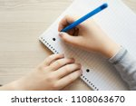 Stock photo kid holding pen and writing in notebook close up top view 1108063670