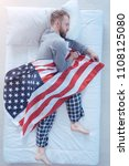 True patriot. Top view on a millennial guy wearing pajamas sleeping tight with an American flag in his hands while taking a nap at home. - stock photo
