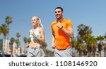 Small photo of fitness, sport and healthy lifestyle concept - smiling couple with heart-rate watch running over venice beach background in california