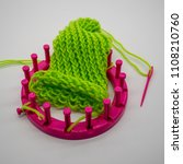 Small photo of Round knitting loom kit and green yarn with basic stitches isolated on white background.