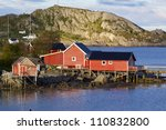 Traditional red fishing rorbu huts by the fjord in town of Reine on Lofoten islands - stock photo