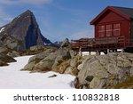 Mountain cabin on Lofoten islands in Norway with sharp mountain peak towering above - stock photo
