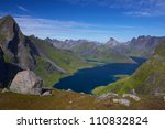 Scenic view of fjord on Lofoten Islands in Norway with dramatic mountain peaks towering above the sea - stock photo