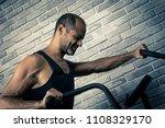 man on exercise bike training... | Shutterstock . vector #1108329170