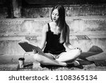 Girl with book sitting on stairs in the park. Black and white photo