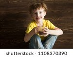 the kid drinking cocoa at home. | Shutterstock . vector #1108370390