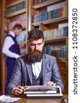 Small photo of Writer working on new book with bookshelves on background. Man with beard and strict face sit in library and work with typewriter, close up. Writers routine concept. Author types novel or poem.
