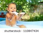 cute baby boy having fun in bubble bath outdoor - stock photo