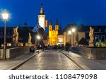 Small photo of Wurzburg, Bavaria/Germany 05/20/2018: Visitors stroll along the All Saint's bridge in the evening, many with glasses of wine in hand.