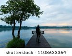 fisherman on wooden pier during ... | Shutterstock . vector #1108633364