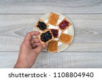 a biscuit with jam in one hand | Shutterstock . vector #1108804940