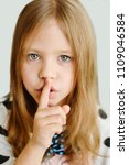 Small photo of girl placing finger on lips asking shh, quiet, silence