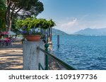 Lake Maggiore, Italy. Lakefront of the town of Meina with a kiosk - bar with tables and beach umbrellas. Itinerary in northern Italy
