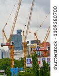Small photo of BANGKOK, THAILAND - July 19, 2017: CMAX luffing tower cranes on construction site in downtown cityscape on background. The Construction and Real Estate Boom Concept.