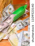 Small photo of Broom sweep a lot of dollar and euro bills in the scoop.