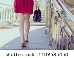 Small photo of Railings balcony terrace direction future blister problem discomfort sidewalk concept. Rear behind back close up photo of happy careless carefree lady carrying pumps in hand, blurred background