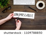 Small photo of From impossible to possible. Do difficult task at work concept. Cutting the part im of written word impossible by sciccors. Office desk. Dark wooden background top view copy space