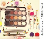 Small photo of set for makeup. Set of many professional visagiste eyeshadow palette red orange green violet pink yellow purple black beige brown colors foundation powder and make-up brushes on white background