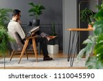 modern man reading book while... | Shutterstock . vector #1110045590