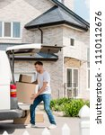 young smiling man moving boxes ... | Shutterstock . vector #1110112676