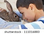 Stock photo boy with a rabbit in the garden at the cottage 111016883