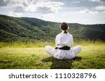 Small photo of Young female athlete in karate kimono sitting on a field. Martial arts.
