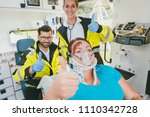 Small photo of Inured woman feeling better after having received first aid giving thumbs up