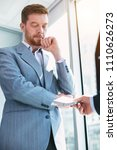 Small photo of Immoral. Serious red-haired businessman wearing a suit and taking a bribe